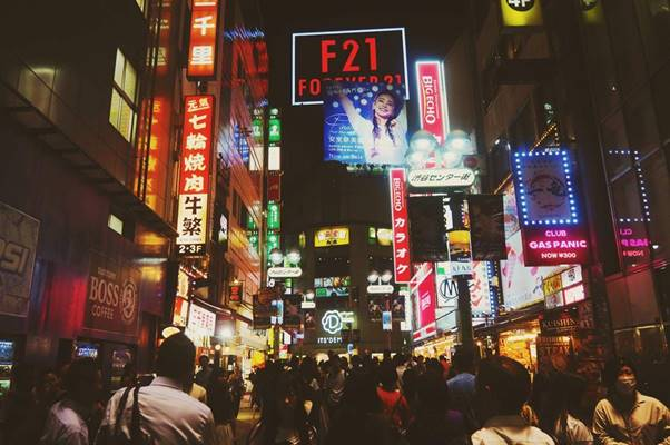Crowd of people under Tokyo's neon signs